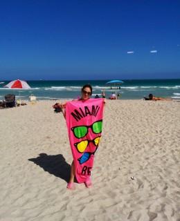 Sarah à Miami, sur la plage avec une serviette rose
